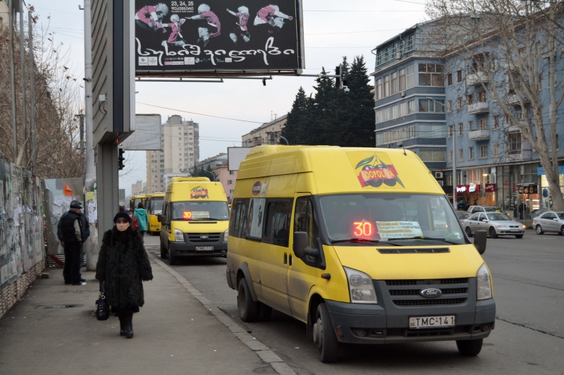 "These yellow minibuses are called ""marshrutkas"", and they are (I believe) the most popular and common form of public transportation in Georgia.  Unfortunately their signs are only in Georgian."